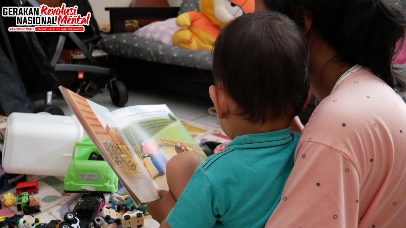 Seorang ibu sedang mensosialisasikan buku pada anak