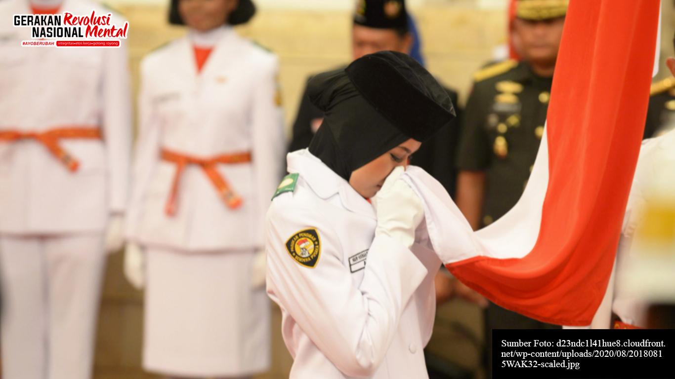 Seorang anggota Paskibraka sedang mencium bendera merah putih