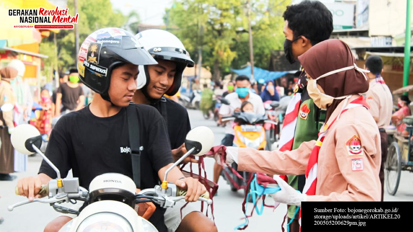 Pramuka membagikan masker kepada pengguna jalan